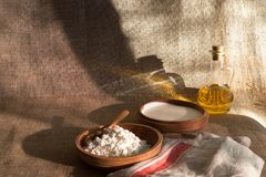 Cottage curd and sour cream in wooden plate on a linen tablecloth Royalty Free Stock Photos