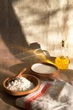 Cottage curd and sour cream in wooden plate on a linen tablecloth Royalty Free Stock Photography