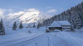 Cottage de montagne près de la forêt dans le paysage d'hiver photos stock