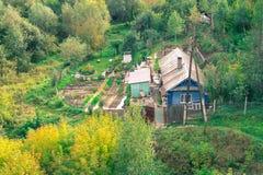 Cottage de pays parmi les arbres automnaux Photo libre de droits