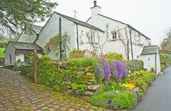 Cottage del paese con i fiori della primavera Fotografia Stock Libera da Diritti