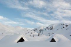 Cottage della montagna coperti in neve Fotografie Stock
