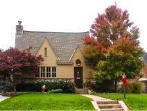 Cottage dello stucco e della pietra con le foglie di autunno un acero giapponese ed archi e corone di Natale Fotografia Stock Libera da Diritti