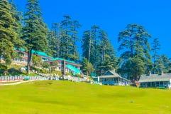 Cottage di concetto di vacanze estive circondati con gli alberi verdi e l'erba verde vicino al parco pubblico con il cielo blu-ch fotografia stock libera da diritti