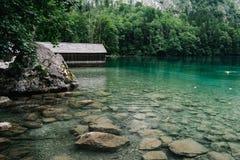 Cottage di legno in bello lago nelle alpi con l'umore nebbioso Immagini Stock