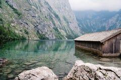 Cottage di legno in bello lago nelle alpi con l'umore nebbioso Immagini Stock Libere da Diritti
