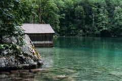 Cottage di legno in bello lago nelle alpi con l'umore nebbioso Fotografia Stock