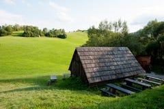 Cottage di legno ed erba verde nel mezzo del nulla Fotografia Stock