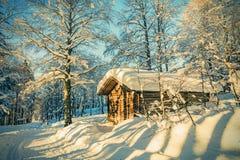 Cottage di legno nella foresta di inverno con gelo e neve nel giorno soleggiato Immagine Stock