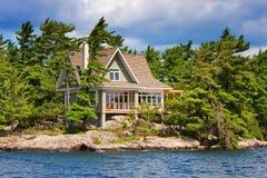 Cottage di legno sul lago immagini stock