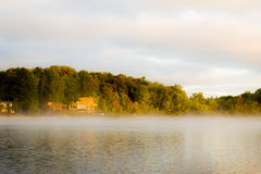 A cottage in the distance on the lake in the light of the sunrise. Royalty Free Stock Photography