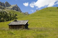 Cottage in dolomites. View of the tops of mountains with small old cottage in front Royalty Free Stock Photo
