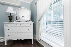 Cottage dresser with mirror. White painted dresser with mirror and lamp near window interior Stock Photo
