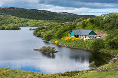 Cottage on Drumbeg lake, Scotland. Stock Photo