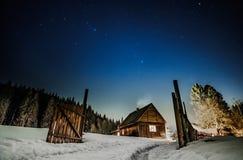 Cottage en bois avec le ciel étoilé bleu la nuit photos libres de droits