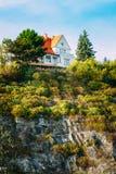 Cottage en bois de maison sur la falaise ou la roche Image libre de droits