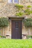 Cottage en pierre anglais avec les portes en bois brunes Images stock