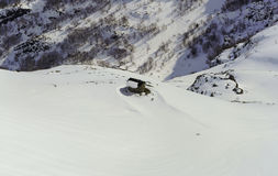 Cottage en pierre parmi les montagnes neigeuses Photographie stock libre de droits