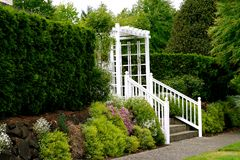 Cottage entryway. Charming and quaint white picket fence with pergola; flower garden; residential scene royalty free stock image