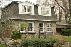 Cottage esecutivo di pietra con il tetto di mansarda Fotografie Stock