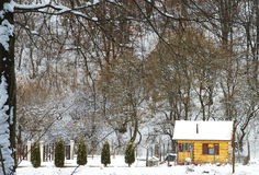 Cottage in the forest. Small cottage in a forest in winter, with small yard Royalty Free Stock Photos