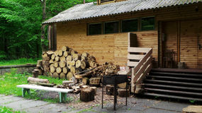 Cottage in forest with grill and firewoods Stock Photos