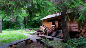 Cottage in forest with grill and firewoods Stock Photography