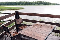 Cottage in forest near river with big wooden terrace. House on the water at the lake, a beautiful bank. Ideal place for. Vacation and holiday. Rain drops on Royalty Free Stock Photo