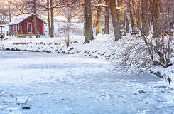 Cottage by frozen pond Royalty Free Stock Photography