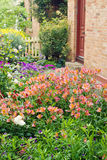 Cottage garden. A pretty, flowering garden with cottage in the background stock photos