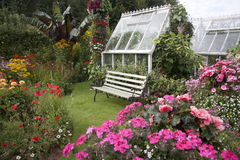 Cottage Garden Seat & Greenhouse Stock Photo