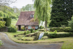 Cottage, Garden and stream. LOOSE, KENT, UK, 11 MAY 2015 - Old cottage with waterfall in the garden, in the pretty village of Loose, Kent, UK Royalty Free Stock Photo