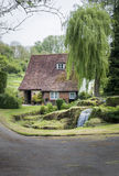 Cottage, Garden and stream. LOOSE, KENT, UK, 11 MAY 2015 - Old cottage with waterfall in the garden, in the pretty village of Loose, Kent, UK Royalty Free Stock Images