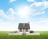 Cottage On Green Lawn. A stone cottage with a chimney and shutters surrounded by a white picket fence on a blue sky and grass lawn background Royalty Free Stock Photos