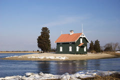 Cottage House on a Peninsula. Green cottage house surrounded with water and snow Stock Image