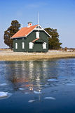 Cottage House on a Peninsula Two. Close view of green cottage house surrounded with water and  ice flowing in the river Stock Photo