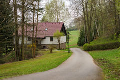 Cottage house with road path nature woods forest countryside landscape Stock Photos