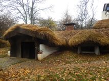 Cottage House with Straws Rooftop National Village Museum in Bucharest, Romania. A traditional cottage house with straws rooftop half built in the ground royalty free stock photography
