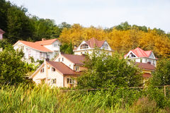 Cottage houses in picturesque autumn forest Royalty Free Stock Photo