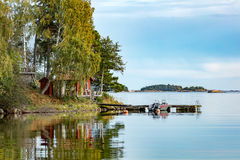 Cottage, jetty and a boat in autumn nature. Calm lake water and blue sky Royalty Free Stock Photo