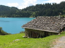 Cottage by the lake. Summer cottage by a lake in the Alps Stock Image