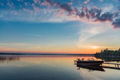 Cottage Lake Sunrise with Boat at Dock in Kawartha Lakes Ontario Canada. Beautiful colours for a cottage sunrise in Ontario with a glassy lake, dock, and boat royalty free stock photo