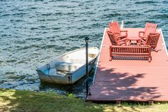Cottage landscape, afternoon sun on the dock and woooden chairs royalty free stock image