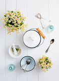 Cottage living decor. Chamomile flowers, white enamelled cookware, glass bottles, vintage spoons on a white wooden background, cozy home rustic decor, vintage Stock Photos