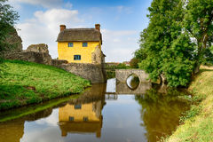 Cottage on a Moat. A pretty thatched cottage built into the ruins of a moated Medieval castle at Stogursey in Somerset stock photo