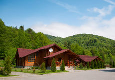 Cottage in the mountain. One modern wooden log cabin with all facilities in the mountains with many trees in the forest during spring time. Against blue sky Stock Photos