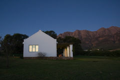 Cottage in the mountains. Cottage with mountains in the background at early evening Stock Image