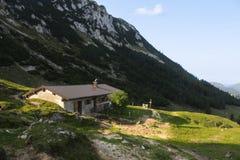 Cottage in mountais dell'Austria - sul prato verde in sushine fotografia stock libera da diritti