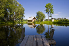 Cottage near pond. With reflection in water, located in Latvia Stock Image