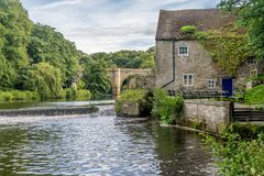A cottage next to river with a stone bridge royalty free stock photography